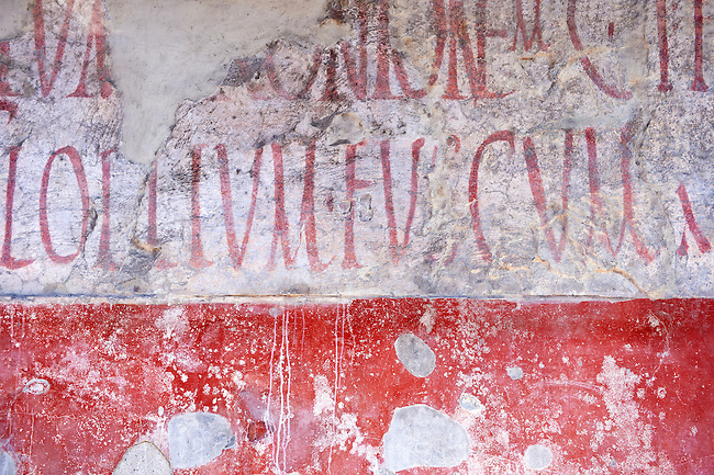 Graffitti on buildings along the Via del Abbondante, Pompeii.