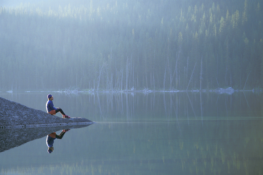 Man sitting on rock reflected in mountain lake, Enchantment Lakes, Washington