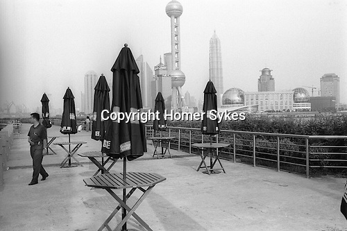 China, Shanghai.   The view from the terrace of the Seagull Hotel terrace looking out across the Huangpu river to the futuristic Pudong skyline.  The Hotel was built in 1985 as an addition to the International Seamen?s Club. Just over the Waibaidu, or Garden Bridge, it is it situated in the former American Concession, incorporated into the International Settlement in 1893...