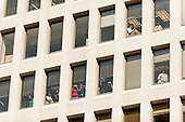 People look on from offices overlooking Pennsylvania Avenue as United States President Barack Obama and U.S. Vice President Joe Biden walk from the White House to Taylor Gourmet on Pennsylvania Ave nearby for a take out lunch.<br /> Credit: Pete Marovich / Pool via CNP