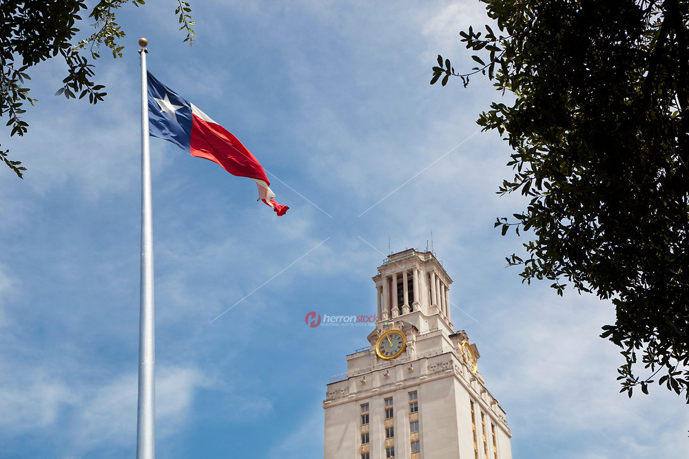 Texas flag flies proudly next to austin higher education tower