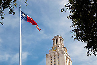 Texas flag flies proudly next to austin higher education tower