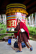 A Bhutanese man prays while turning the prayer wheel outside the Ramtanka Temple in Paro, Bhutan. Photo: Sanjit Das/Panos
