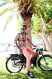 BERMUDA, Hamilton. Chef Marcus Samuelsson on a vintage scooter in Barr's Bay Park located in downtown Hamilton. The Hamilton Harbour is in the background.