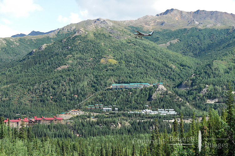 "Multiple hotels are clustered near the entrance to Denali National Park in an area Alaskans call ""Glitter Gulch."" Here a sightseeing plane flies over the area. The Alaska Railroad's Denali Star train runs between Anchorage and Fairbanks, with Denali one of the stops along the way."