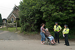 Balcombe West Sussex UK. Local resident and carer chatting to police women, outside the church parish hall.