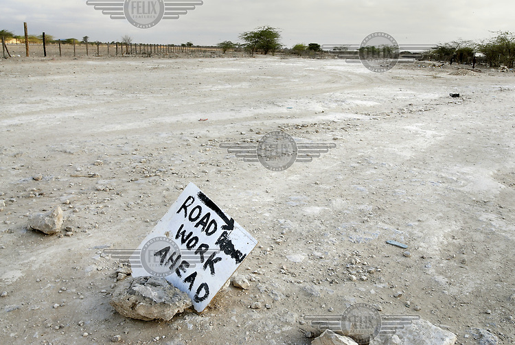A hand-painted sign reading 'road work ahead' is propped up by a rock at the edge of a dusty track, in a region which lacks basic infrastructure.