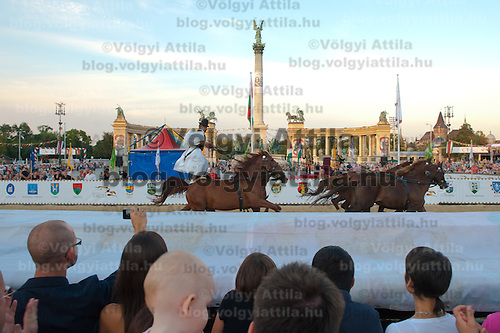"Man performs the world renowned Hungarian riding formation ""Puszta five"" when a rider standing on the backs of two horses controls a total of five animals during the National Gallop held on Heroes' Square in Budapest, United Kingdom on September 17, 2011. ATTILA VOLGYI"