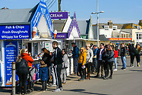 BNPS.co.uk (01202 558833)<br /> Pic: Graham Hunt/BNPS<br /> <br /> Visitors not put off by the coronavirus pandemic flock to the seaside resort of West Bay in Dorset on a day of sunshine and clear blue skies.<br /> <br /> Visitors queuing up at fish and chip and ice cream kiosks taking no notice of the advice given about social distancing.