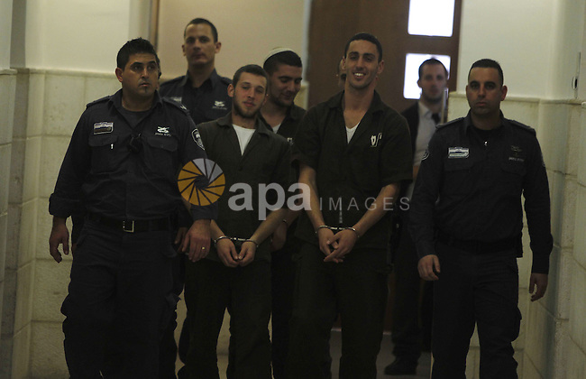 """Three Israeli suspects, members of the right-wing Lehava organisation, are escorted by security to a hearing at the District Court in Jerusalem on December 15, 2014. The three are suspects behind an arson attack last month that targeted a Jewish-Arab school in Jerusalem on November 29, badly damaging a classroom and slogans in Hebrew, including """"Death to Arabs"""", were written on the walls. Photo by Muammar Awad"""