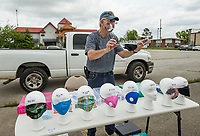 Terry Ackley of Rogers displays a mask for a customer Thursday, May 14, 2020, in a vacant parking lot next to Harbor Freight Tools in Rogers. Ackley is selling hand sanitizer and a variety of masks including fabric masks made by his roommate, disposable surgical masks and commercial filter masks. He plans to be set up Friday as well. Go to nwaonline.com/200515Daily/ to see more photos.<br /> (NWA Democrat-Gazette/Ben Goff)
