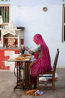 Indian woman in Rajasthani sari works at home using sewing machine in Nimaj village, Rajasthan, India