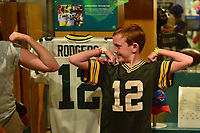 Canton, OH - August 4, 2018: At the Pro Football Hall of Fame Museum in Canton, OH, August 4, 2018, a boy wearing an Aaron Rodgers jersey flexes next to an actual jersey worn by Rodgers. (Photo by Don Baxter/Media Images International)