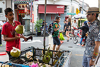 George Town, Penang, Malaysia. Coconut Vendor Cutting a Coconut for Customer.