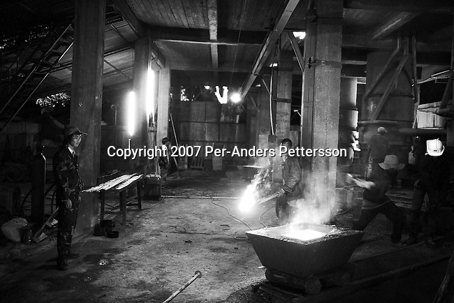 NDOLA, ZAMBIA MARCH 24: Pan-De, age 23, a Chinese supervisor, stands with unidentified Zambian workers as they toil in a copper smelter on March 24, 2007 in Ndola, Zambia. Eastern Union Limited is a China based company who buys Copper from Congo DRC, and brings it to Ndola to their Copper smelter. The smelter was shipped from China and operates 24 hours a day in an Industrial area in Ndola. The copper is eventually trucked to Dar es Salaam in Tanzania and on ships to China. The Chinese industry's thirst for raw materials has seen metals prices increase a lot the last years. Tens of thousands of Chinese has come to Africa the last years to work in infrastructure projects and businesses. Chinese companies are often the lowest bidders for contracts, pricing out the more expensive European companies. The Chinese people often live where they work and rarely interact with the local population. Most Chinese don't speak English and they are mostly staying in the compounds cooking their Chinese food, and watching Chinese Television and DVDs. (Photo by Per-Anders Pettersson)...