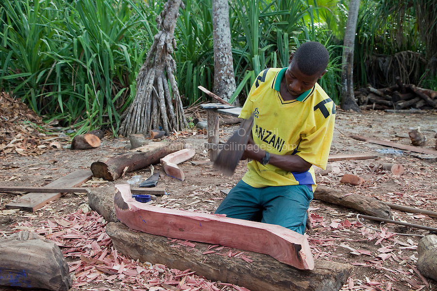 Nungwi, Zanzibar, Tanzania.  Dhow Construction.  Carpenter using an adze to shape an internal hull support.