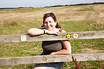 Middle aged woman smiling sitting on stile on country footpath Burrow Hill, Boyton, Suffolk, England, UK - model released