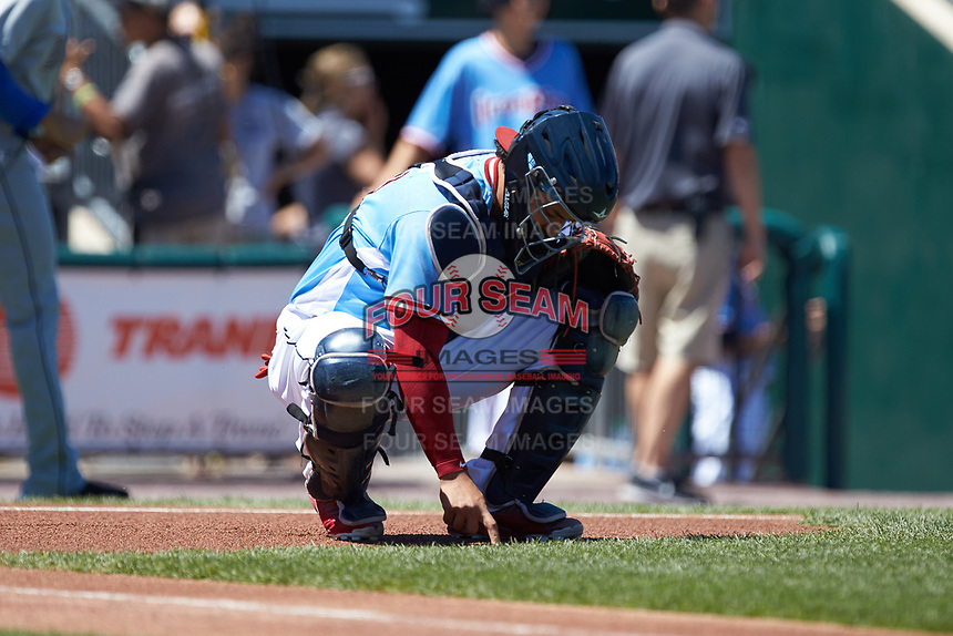 Lehigh Valley Iron Pigs catcher Jorge Alfaro (24) writes a message in the dirt in front of home plate prior to the game against the Durham Bulls at Coca-Cola Park on July 30, 2017 in Allentown, Pennsylvania.  The Bulls defeated the IronPigs 8-2.  (Brian Westerholt/Four Seam Images)