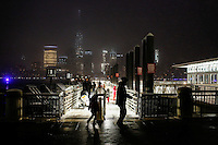 The lower Manhattan and the World Trade Center are seen while people walk on a path covered with snow at the ferry station in Exchange Place in New Jersey, 01/17/2016 Photo by VIEWpress