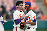 Starting pitcher Keyshawn Askew (46), right, of the Clemson Tigers, is greeted by Davis Sharpe after throwing a scoreless inning in a game against the Charlotte 49ers on Monday, February 18, 2019, at Doug Kingsmore Stadium in Clemson, South Carolina. Clemson won, 7-6. (Tom Priddy/Four Seam Images)