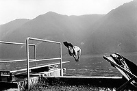 Switzerland. Canton Ticino. Castagnola. A man jumps in the lake from a diving board. He wears a swimsuit and palms on both feet. Castagnola is distant 10 minutes from Lugano. Lake Lugano (Italian: Lago di Lugano or Ceresio) is a glacial lake which is situated on the border between southern Switzerland and Northern Italy. © 1995 Didier Ruef