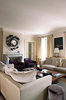 A photograph by Antoine Schneck competes with a mirror above the fireplace by Van der Straeten in this elegant contemporary living room