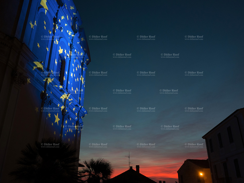 """Italy. Liguria Region. Ospedaletti. Christmas day. An european flag on the catholic church at sunset. The Flag of Europe, or European Flag, is the official symbol representing Europe. Consisting of a circle of 12 golden (yellow) stars on an azure background, it was first adopted in 1955 by the Council of Europe (CoE) to represent the European continent as a whole. Later being adopted the European Union (EU), the flag is sometimes colloquially known as the """"flag of the European Union"""", however this term is not official as the flag represents more broadly, the identity and unity of Europe. 25.12.16 © 2016 Didier Ruef"""