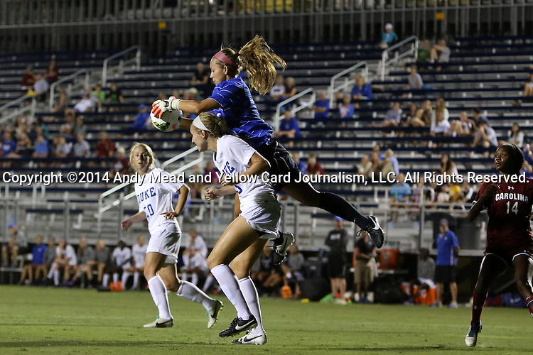 14 August 2014: Duke's EJ Proctor (in blue) grabs the ball over Kara Wilson (below). The Duke University Blue Devils hosted the University of South Carolina Gamecocks at Koskinen Stadium in Durham, NC in a 2014 NCAA Division I Women's Soccer preseason match. Duke won the exhibition 2-0.
