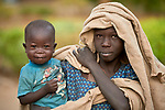 A girl carries her small sibling in Gidel, a village in the Nuba Mountains of Sudan. The area is controlled by the Sudan People's Liberation Movement-North, and frequently attacked by the military of Sudan.