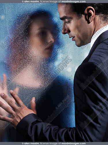 Emotional portrait of a young man and a woman separated by a wet glass pane. Couple relationship concept.