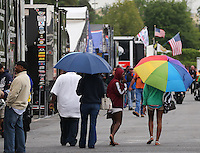 May 3, 2013; Commerce, GA, USA: Spectators walk beneath umbrellas through the NHRA pro pits during a ran delay to qualifying for the Southern Nationals at Atlanta Dragway. Mandatory Credit: Mark J. Rebilas-