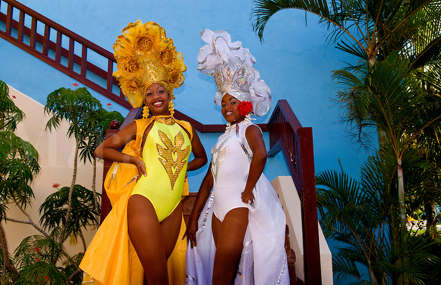 Beautiful dancers in costume against blue wall with headresses in the old colonial city of Trinidad in Cuba
