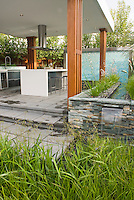 Outdoor Kitchen & Covered Patio home landscaping with dining table, waterfall water feature, ornamental grasses plants, hood, modern design, stairs steps, deck, sink, refrigerator, oven, classy and sophisticated room for cooking and eating outside