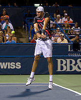 John Isner hits a backhand during the Legg Mason Tennis Classic at the William H.G. FitzGerald Tennis Center in Washington, DC.  Unseeded Xavier Malisse defeated American John Isner in three sets in a thunderstorm delayed evening session.