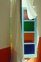 A simple length of material is draped around this window with stained glass panes