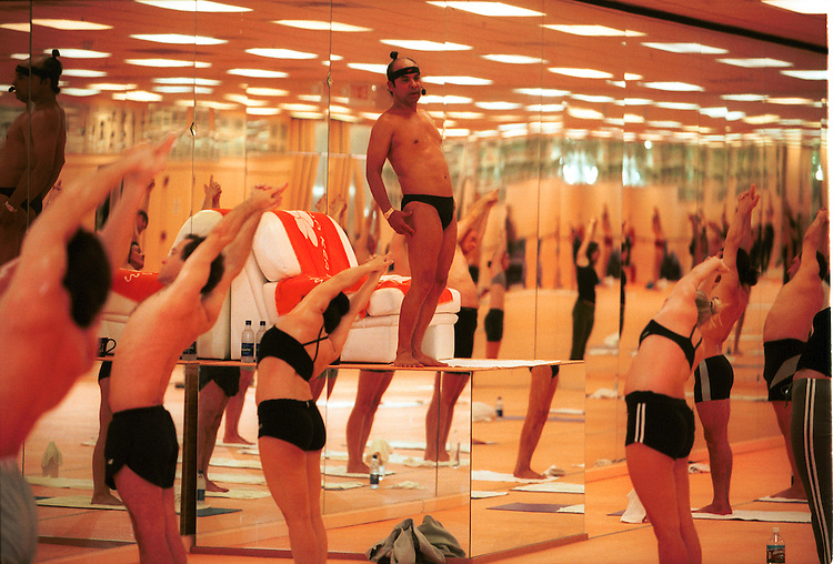 In the comfort of a soft chair, Bikram Choudhury, the 55-year-old California guru who invented Bikram yoga, leads devotees through 90 minutes of yoga positions in a room heated to 105 degrees at his Los Angeles CA studio 22 January 2003. Photo: Gerard Burkhart