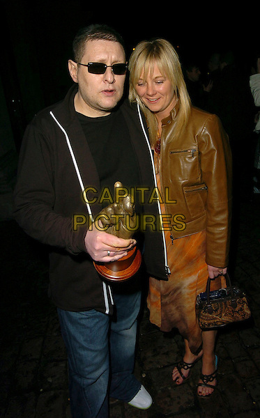 SHAUN RYDER & GUEST.At the NME Awards After Show Party, .Hammersmith Palais, London, England, .February 23rd 2006..full length sean award trophy sunglasses .Ref: CAN.www.capitalpictures.com.sales@capitalpictures.com.©Can Nguyen/Capital Pictures