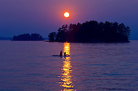 Girls watching a sunset in Lake Muskoka<br /> Muskoka Beach<br /> Ontario<br /> Canada