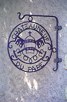 A wrought iron sign hanging on a wall with the text Chateauneuf du Pape and the pope's mitre and saint peter's keys  Chateauneuf-du-Pape Châteauneuf, Vaucluse, Provence, France, Europe  Chateauneuf-du-Pape Châteauneuf, Vaucluse, Provence, France, Europe