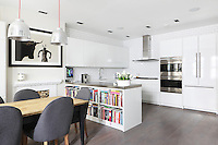A bookcase almost overflows with recipe books in this open-plan kitchen/dining area of a Laverton Mews house in London