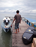 Indonesia, rear view of man holding rope tied with boat at dock