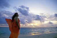 EDITORIAL ONLY. Teacher (kumu) chants (oli) at sunrise. Lanikai Beach, Oahu