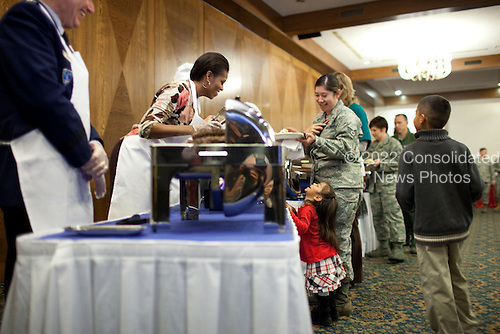 First Lady Michelle Obama leans over the trays to talk with a little girl as she helps serve food to U.S. airmen and women and their families at Ramstein Air Base in Ramstein, Germany, November 11, 2010. .Mandatory Credit: Chuck Kennedy - White House via CNP