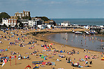 Broadstairs Kent Uk. Viking bay beach tourists on their annual summer holidays. Bleak House over looking the bay.