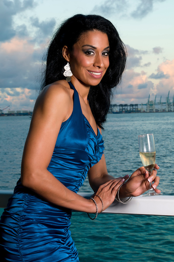 Happy hispanic woman drinking champagne in a terrace with ocean view.