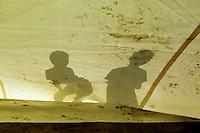 """Nach dem Erdbeben im August in der Tuerkei leben tausende Menschen in Zeltlagern und Behilfszelten.<br /> Die Hilfsorganisation """"Kinder haben Rechte"""" hat in der Ortschaft Yuvacik-Koey eine Traglufthalle aufgebaut, die fuer die Kinder als Schulhaus dienen soll, da nicht klar ist, ob und wann die Regierung ein neues Schulhaus errichtet.<br /> Hier: Schatten von Kindern, die von aussen das erste Aufblasen ihrer """"Ballon-Schule"""" verfolgen.<br /> 13.10.1999, Yuvacik-Koey/Tuerkei<br /> Copyright: Christian-Ditsch.de<br /> [Inhaltsveraendernde Manipulation des Fotos nur nach ausdruecklicher Genehmigung des Fotografen. Vereinbarungen ueber Abtretung von Persoenlichkeitsrechten/Model Release der abgebildeten Person/Personen liegen nicht vor. NO MODEL RELEASE! Nur fuer Redaktionelle Zwecke. Don't publish without copyright Christian-Ditsch.de, Veroeffentlichung nur mit Fotografennennung, sowie gegen Honorar, MwSt. und Beleg. Konto: I N G - D i B a, IBAN DE58500105175400192269, BIC INGDDEFFXXX, Kontakt: post@christian-ditsch.de<br /> Bei der Bearbeitung der Dateiinformationen darf die Urheberkennzeichnung in den EXIF- und  IPTC-Daten nicht entfernt werden, diese sind in digitalen Medien nach §95c UrhG rechtlich geschützt. Der Urhebervermerk wird gemaess §13 UrhG verlangt.]"""