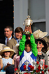 Jockey Edgar Prado holds the trophy in the winners circle at Churchill Downs in Louisville, Kentucky on May 6, 2006.  Barbaro, ridden by Prado, won the race....