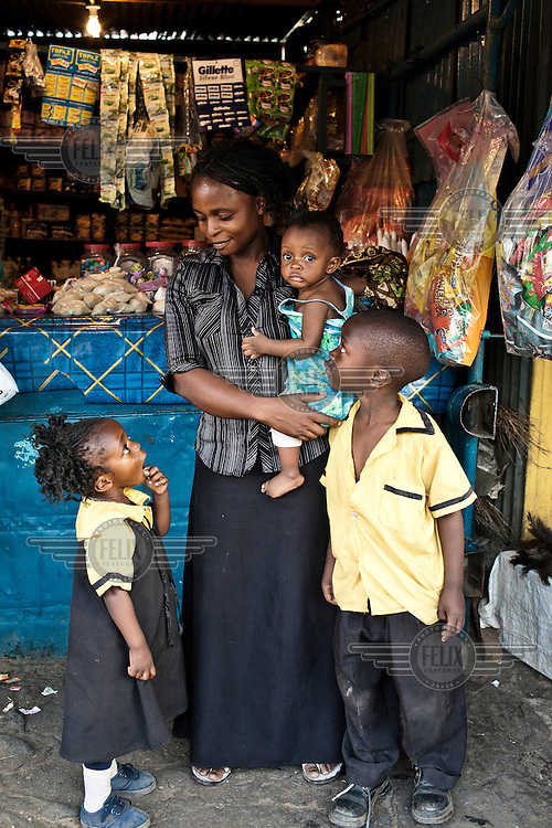 Caroline Machanga with her three yougest children,  Kelvin (7), Memory (3) and Melody (7 mths), beside her stall in Nakambala Market.