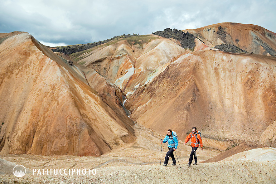Two trekkers hiking in the brown, earth toned landscape of Landmannalaugar, Iceland