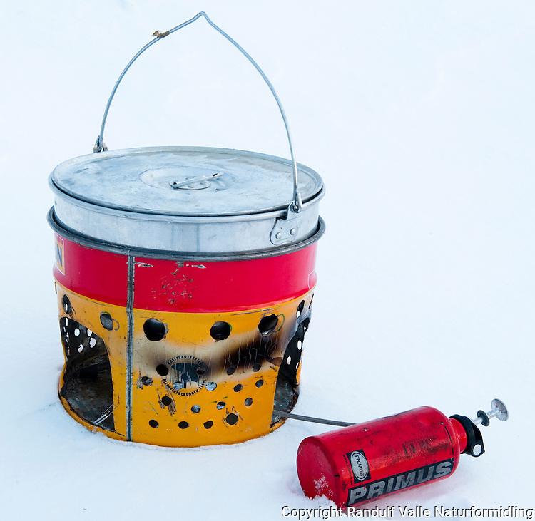 Kjele og primus med malingsspann som vindskjerm. ---- Primus stove using paint bucket as wind screen.